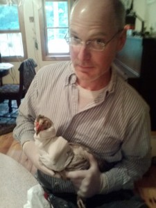 "Clark holding his prize Flarry Eye Gray hen following the amputation of her broken left wing. She survived and has been renamed ""Lefty."""